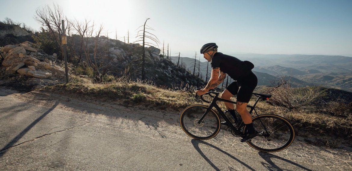 Cyclist climbing mountain on a road bike